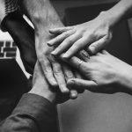 Imagem de pessoas unindo as mãos simbolizando team coaching