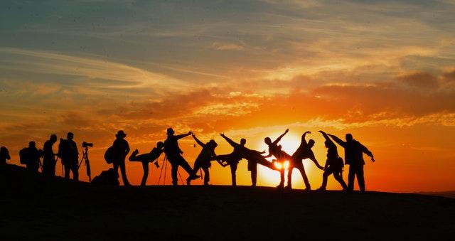 Imagem de pessoas juntas no pôr do sol simbolizando team coaching