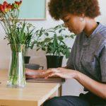 mulher negra sentada à mesa mexendo em tablet simbolizando a necessidade de trabalho remoto durante a pandemia do novo coronavírus