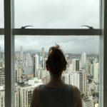 Mulher em frente à janela com vista para a cidade simbolizando a crise do coronavírus e o isolamento social